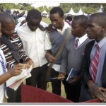 Mercy in white shirt and a tie talking to students on agriculture and agribusiness.